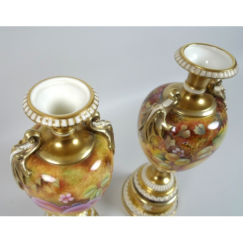 65 - A pair of modern Royal Worcester pedestal vases, foliate clasped twin handles, decorated in a 'Hand ...