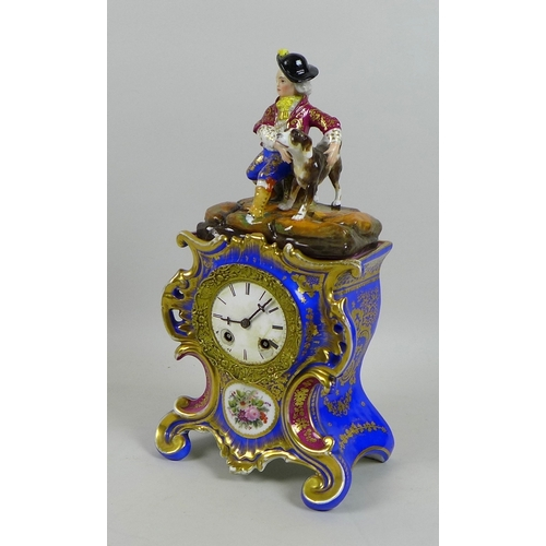 71 - A late 19th century porcelain figural mantel clock in glass dome, with blue ground gilt highlighted ...