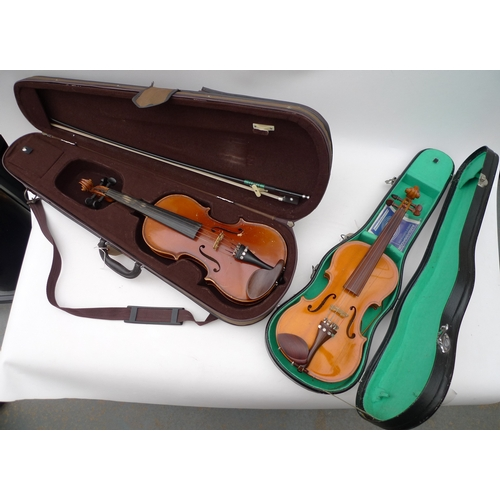 9 - Two violins, one a 3/4 size German violin with bow, the other a Blessing 1/2 size violin, both in ha...