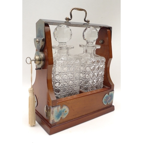 25 - A tantalus with two cut glass decanters....