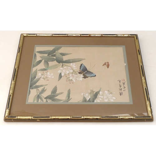 41 - A 19th century Japanese silk painting depicting butterflies amidst blossoms, framed....