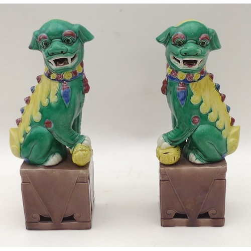 70 - A pair of 20th century Dogs of Fo, polychrome painted on buff coloured bases, 26cm high....