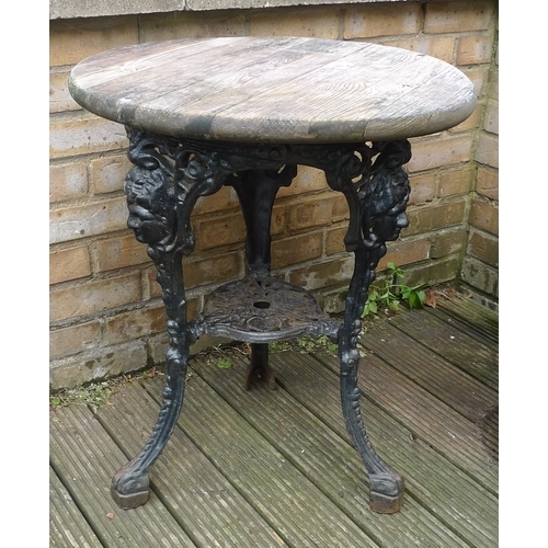 135 - A Victorian style cast iron pub table, the black painted base with three legs, having masks to the t...