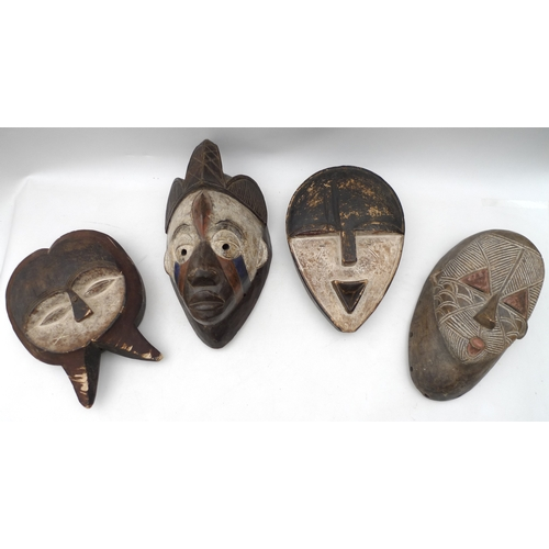 153 - A group of four carved and painted 20th century reproduction tribal African masks, mostly from West ...