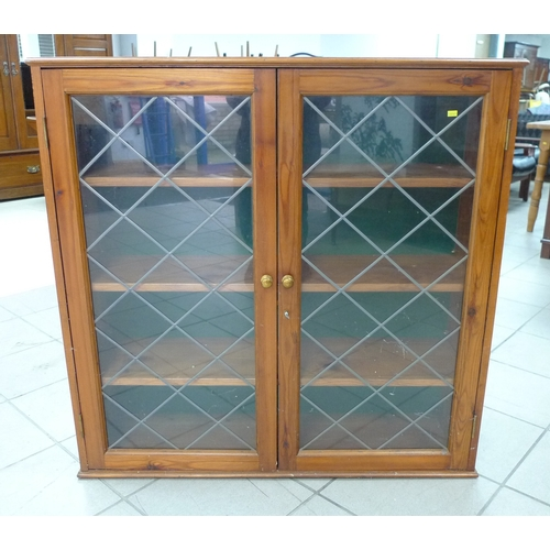 162 - A modern pine glazed cupboard, with twin leaded style paned doors, brass knobs and three shelves....
