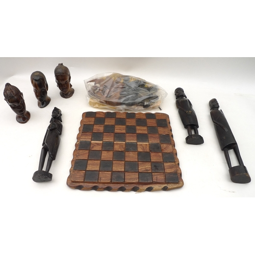 166 - A collection of carved wooden African items, including a chess board with full set of chess pieces, ...