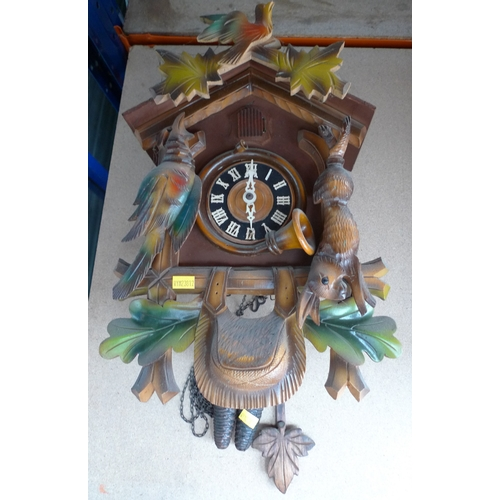 240 - A carved wooden cuckoo clock with painted coloured foliage, with pendulum and two weights cast as pi...