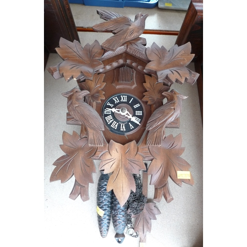 244 - A carved wooden cuckoo clock, with birds and foliage, pine cone weights, with pendulum, 36cm....