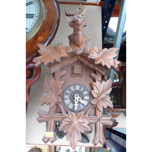 247 - A carved wooden cuckoo clock, with stag's head surmount and white applied Roman numerals, with pendu...
