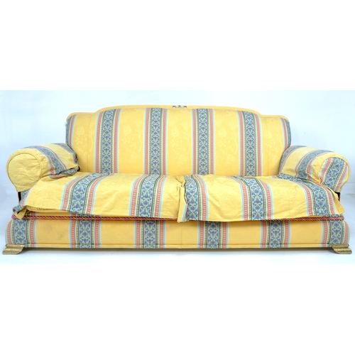 304 - A modern three seater sofa with brass feet, yellow cotton upholstered with striped detailing....