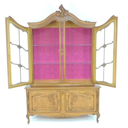 305 - A French oak glazed display cabinet, twin doors opening to reveal two glass shelves, the base sectio...