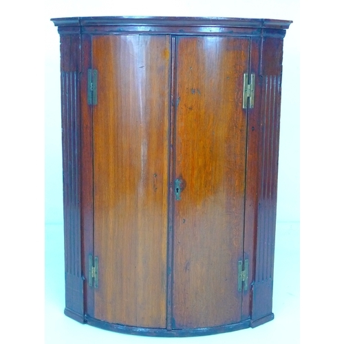 344 - A Georgian barrel fronted corner cupboard, reeded detailing to either side of the doors, later green...