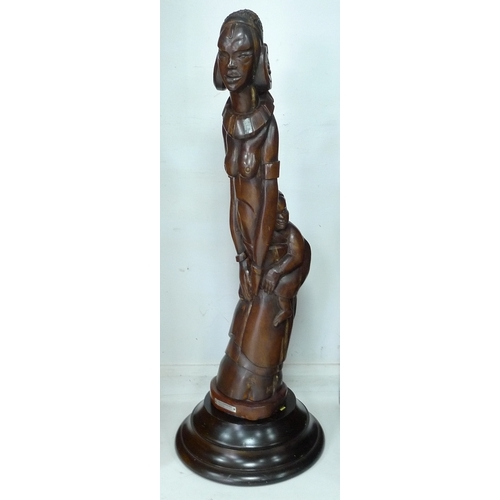 348 - A large modern wooden figural carving, applied plaque to circular base 'Kikiuyu Woman & Child, Cork ...