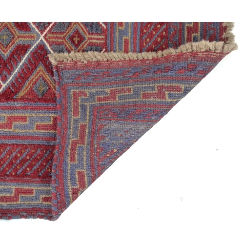 309 - A Gazak rug with diamond pattered field, dark red and blue, divided by white stripes, 130 by 115cm....