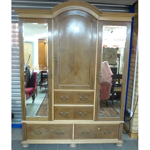 310 - An Edwardian mahogany compactum wardrobe, with two mirrored doors flanking central single door and t...