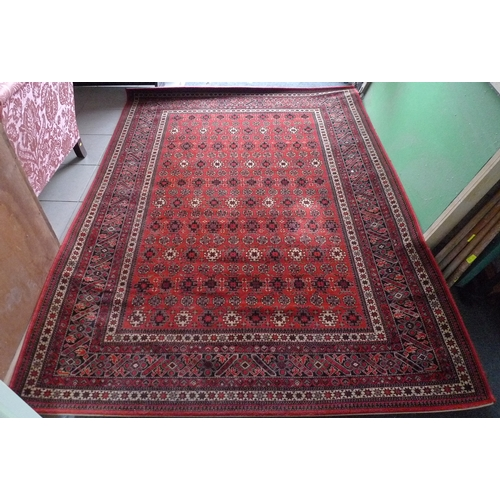 355 - A modern red ground rug, 170 by 240cm....