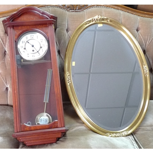 356 - A modern wall clock and oval gilt framed mirror, also modern....