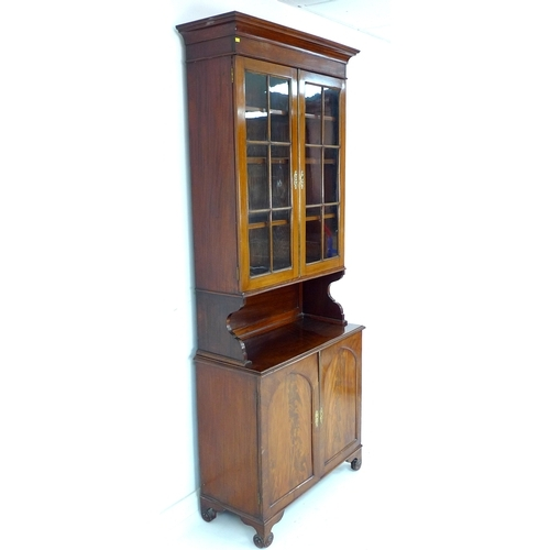317 - An early 19th century mahogany display cabinet, the twin glass paned doors enclosing shelves with br...