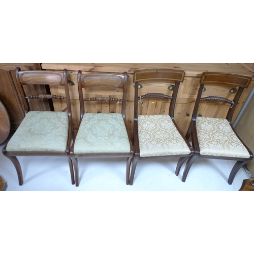 322 - A set of four Regency mahogany sabre legged dining chairs, with crossbanded decoration, cream fabric...