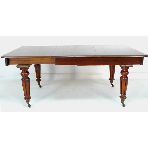 323 - An early 19th century mahogany extending dining table, with two additional leaves, raised on turned ...