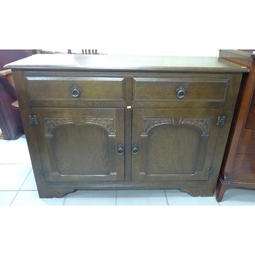 326 - An Old Charm style sideboard, circa 1970, with two drawers and two cupboards....