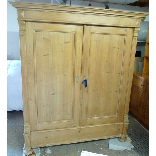 406 - A French 19th century stripped pine armoire, two full length doors enclosing a hanging space....