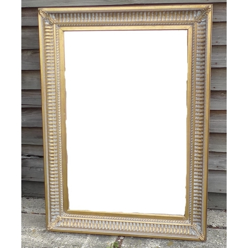 468 - A modern wall mirror with rectangular plate, in gilt and moulded Arquadia frame....
