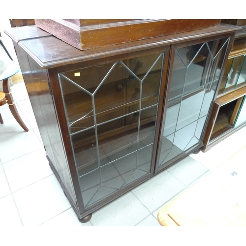 366 - A pair of mid 20th century stained oak bookcases, each with twin leaded glazed doors enclosing two s...