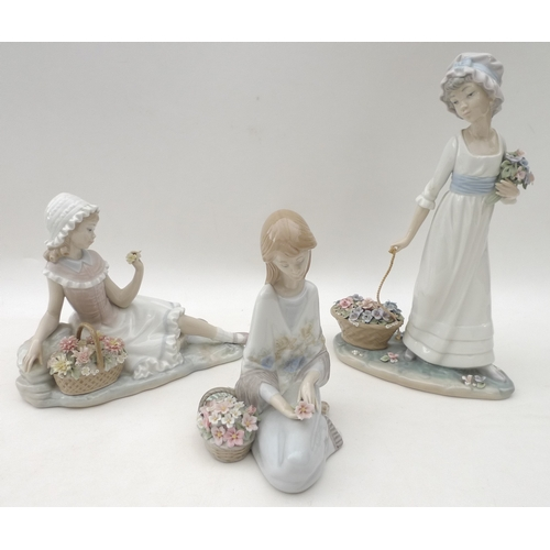 30 - A group of three Lladro ceramic figurines, modelled as young girls with baskets of flowers, 28cm, 18...