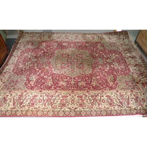315 - A Persian carpet, with red ground, decorated in green and cream with a large central medallion surro...