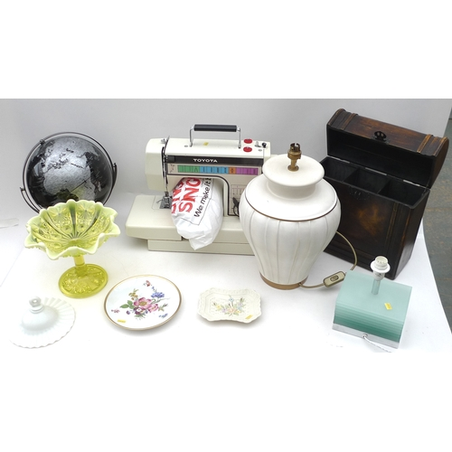 110 - A Singer electric sewing machine, a modern wine carrier, with hinged lid, a tabletop globe, two smal...