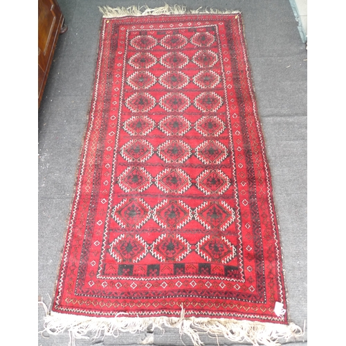 363 - A Persian red ground rug, with nine rows of three black and white geometric medallions, multiple bor...