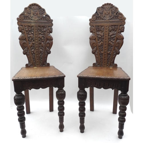 176 - A pair of Victorian Arts and Crafts style oak hall chairs with carved backs and caryatyd sides aroun...