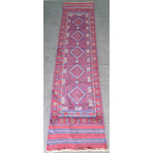 392 - A Meshwari runner, with red and blue geometric ground, five white edged diamond medallions, five str...