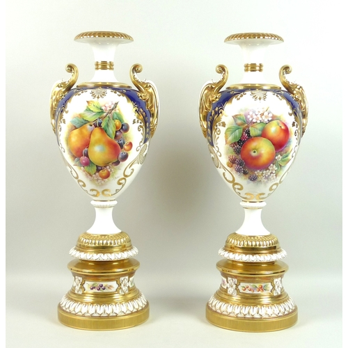 60 - A pair of large modern Royal Worcester pedestal vases, foliate clasped twin handles, decorated in a ...