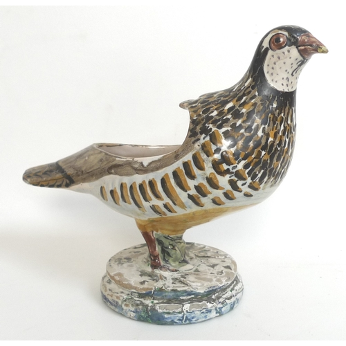 36 - An 18th century Spanish faience sauce boat by Alcora, modelled in the form of a quail, the body poly...