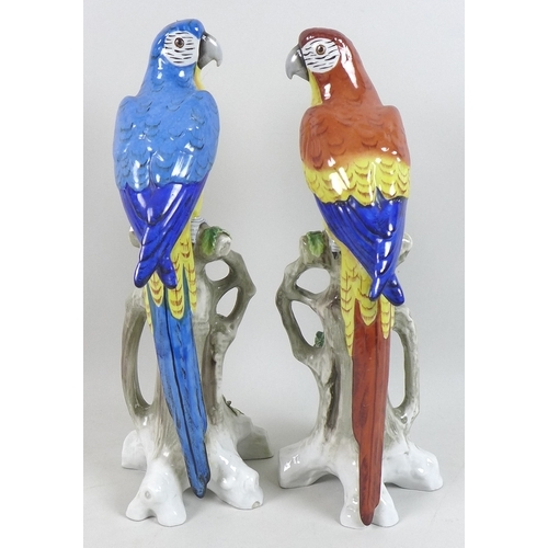 11 - A pair of Sitzendorf figurines, modelled as parrots, each standing on a naturalistic branch with app...