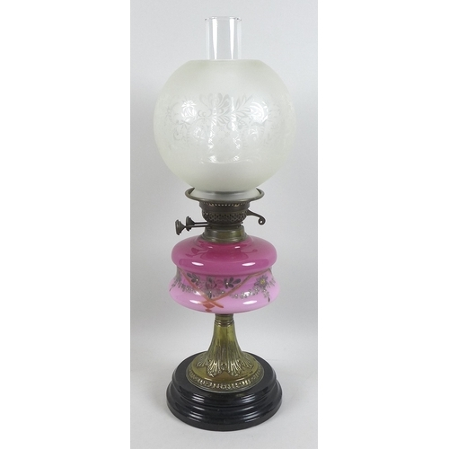 99 - Two Victorian oil lamps, with pink pink glass reservoirs, painted decoration, brass columns and blac...