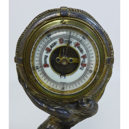 69 - A late 19th or early 20th century barometer, unusually formed as a mermaid holding a lifebuoy aloft,...