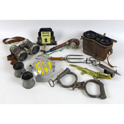 84 - A group of Victorian and later collectables, including a pair of handcuffs with key, an AA car badge...