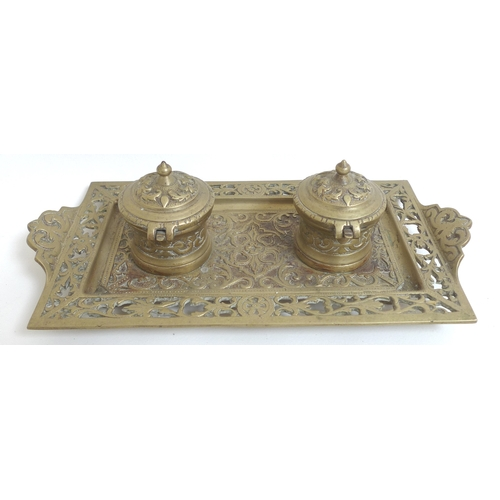 83 - A group of three brass desk stands, each with cast decoration, one with twin inkwells on tray shaped...