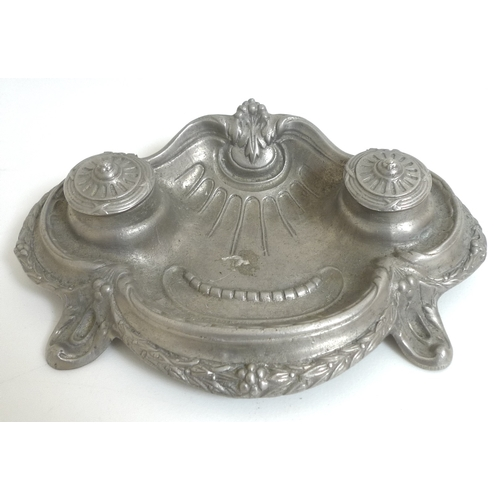82 - Two cast white metal desk stands, one with cast foliate swag decoration and twin inkwells, the other...