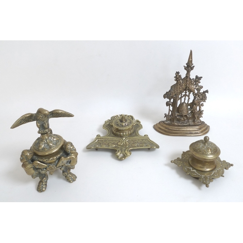 90 - A group of three brass desk stands, one of lidded urn form supported by three winged monopodia, the ...