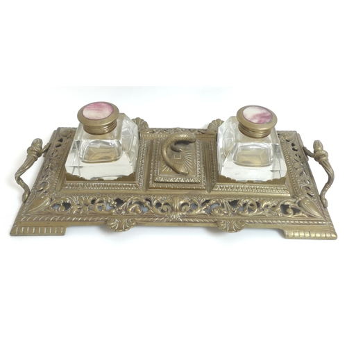 92 - A Victorian brass desk stand, with twin cut glass inkwells, central lidded compartment with snake ha...