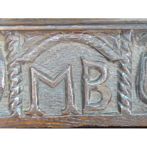 298 - An early 19th century oak cupboard, carved frieze with initials 'MB', two panel doors, one with carv...