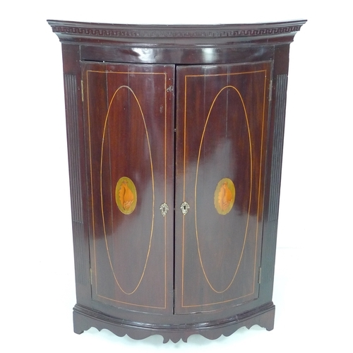 275 - A George III mahogany and inlaid corner cupboard, bow front with twin doors inlaid with shell patera...