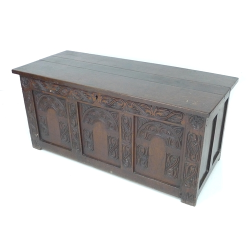 291 - A 19th century oak chest, with lift lid and three panel carved front, 119 by 49.5 by 54cm high....