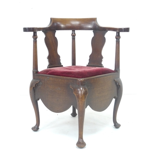 276 - An early 19th century mahogany corner chair, shaped outscrolling arms, vase and turned splats, red v...