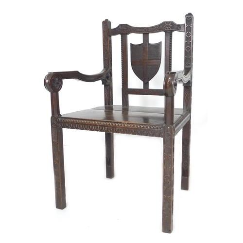 290 - A Gothic Revival solid oak open arm chair, early 20th century, with blind carved frame, shield back,...