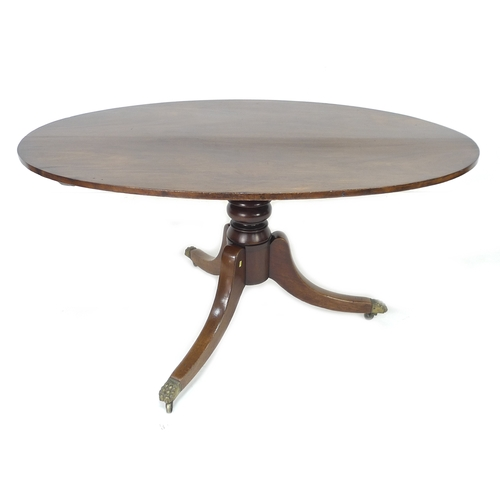 243 - A Regency style mahogany table, with oval surface, turned column raised on three outswept legs, bras...